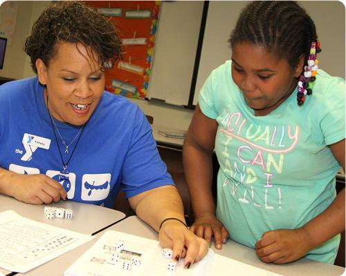 Photo of a Y Club leader using dice to play a learning game with a student