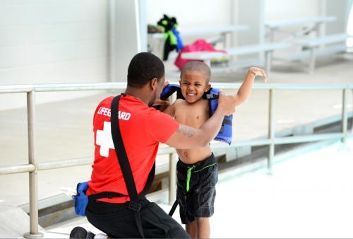 Photo of a lifeguard helping a young boy put on a life jacket