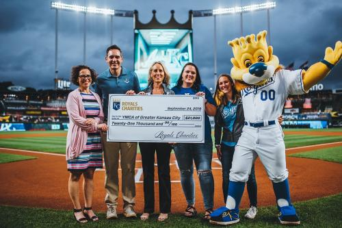 YMCA representatives receive $21,000 check from Royals Charities and Sun Life's Strikeout Diabetes Campaign on the field at a Royals game.